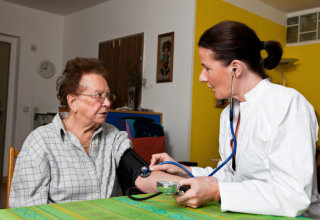 nurse checking blood pressure of old woman
